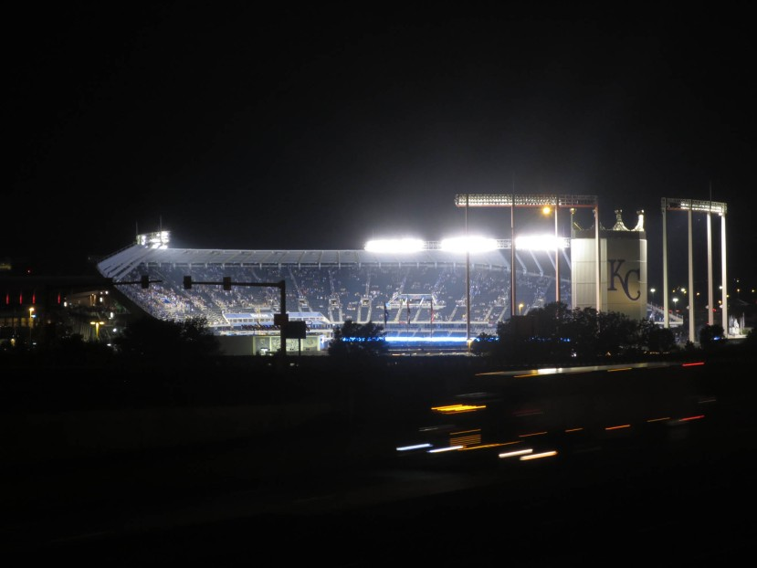 36_kauffman_stadium_from_afar_at_night_with_a_truck_streaking_past