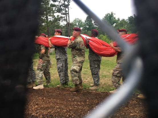 31_sneak_peek_through_fence_of_soldiers_carrying_huge_american_flag